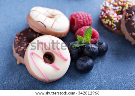Small glazed mini donuts with fresh raspberries and blueberries - stock photo