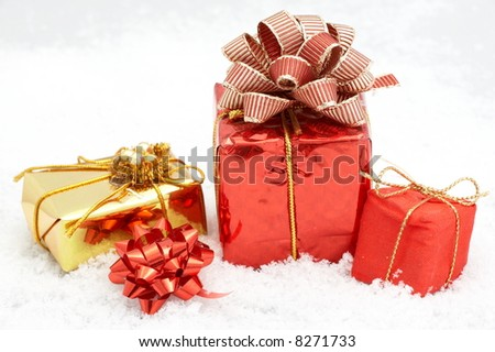 small golden and red gift boxes in the snow - stock photo