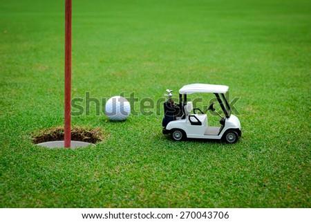 Small golf car figure on green - stock photo