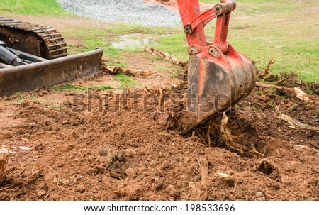 Small grader and brown soil - stock photo