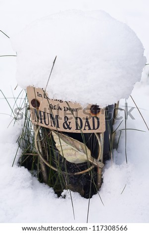 Small grave covered with snow at cemetery dedicated to someone's buried parents - stock photo
