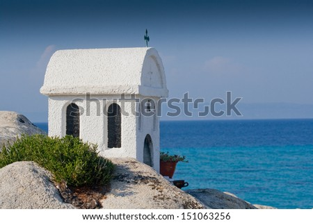 Small Greek chapel with blue sky - stock photo