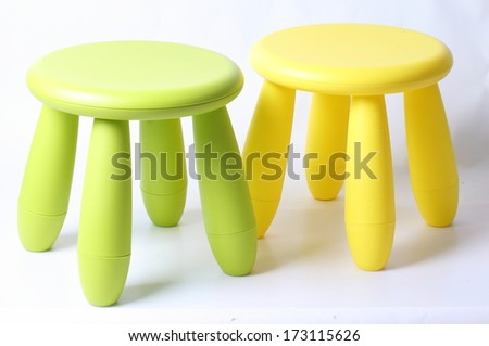 Small green and yellow plastic stool for kids isolated on white