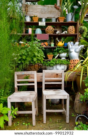 small green garden with many decorations and two wooden chairs - home exterior - stock photo