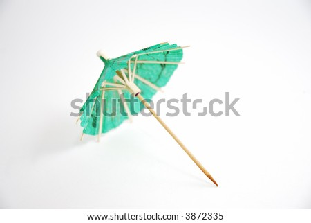 Small green paper umbrella for cocktails, macro close up, isolated on white