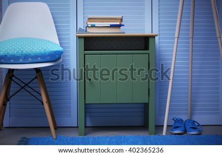 Small Green Table With Books And Chair Near Blue Wooden Wardrobe