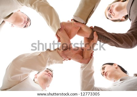 Small group of business people joining hands, low angle view. - stock photo