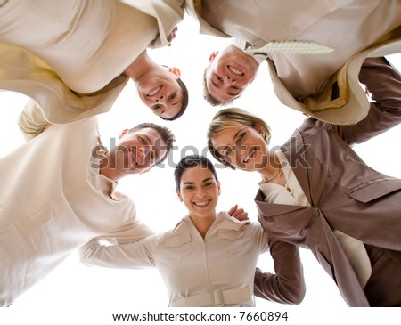 Small group of business people standing in huddle, smiling, low ange view. - stock photo