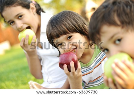 Small group of children eating apples together, shallow DOF - stock photo