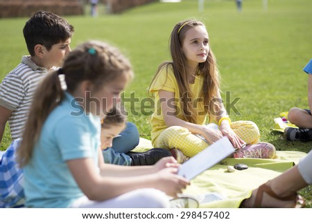 Small group of children sitting on the grass having a lesson outdoors. The children look to be listening and enjoying themselves.  - stock photo