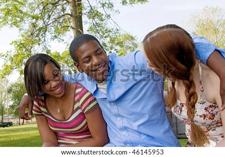 small group of 3 multi-ethnic friends playing in the park and laughing together having fun - stock photo