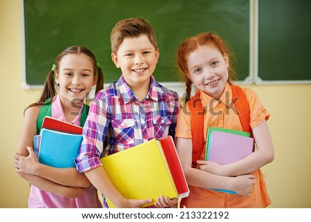 Small group of school friends looking at camera on background of blackboard - stock photo