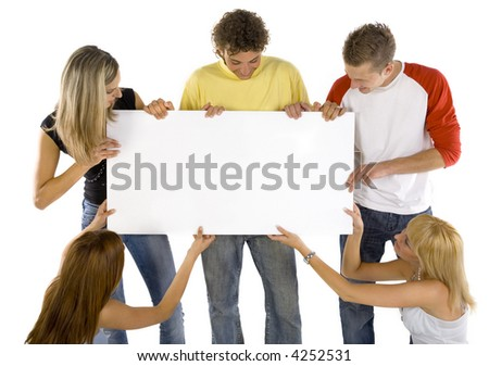 Small group of teenagers holding white blank board. Looking at it. White background, front view - stock photo