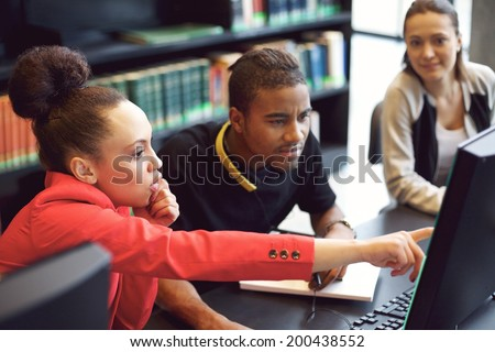 Small group of university students working on computer in a library. Young people finding information for their college assignment. - stock photo