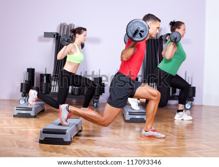 Small group of young people doing a leg exercise in aerobics class - stock photo