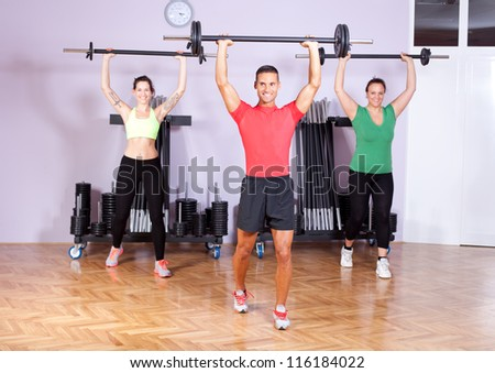Small group of young people doing shoulder exercises in aerobics class - stock photo