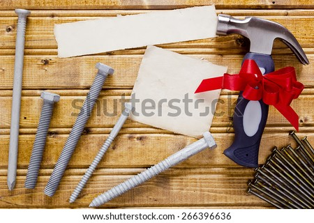 Small hammer with a red bow as a gift for Father's day. - stock photo