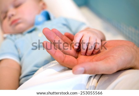 small hand the sleeping baby in the palm of a parent. close-up - stock photo