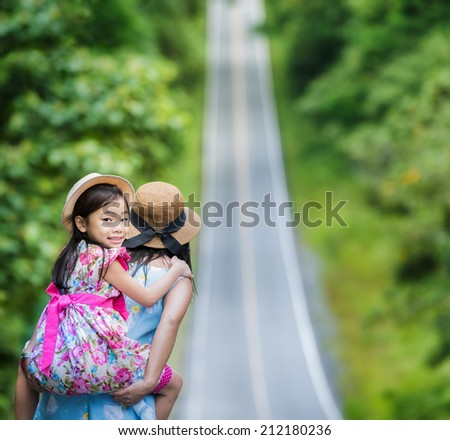 Small happy girl enjoying a piggyback ride on his mothers back and walk on the road. - stock photo