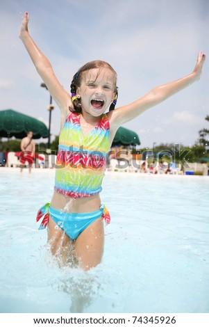 Small happy girl enjoys hot summer day at swimming pool.
