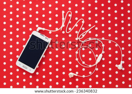 Small headphones with mobile phone on red paper with dots - stock photo