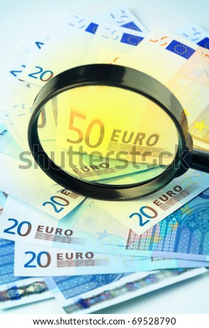 Small heap of Euro currency under a magnifying glass, - stock photo