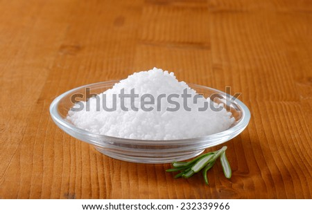 small heap of salt in the glass bowl with thyme sprig - stock photo