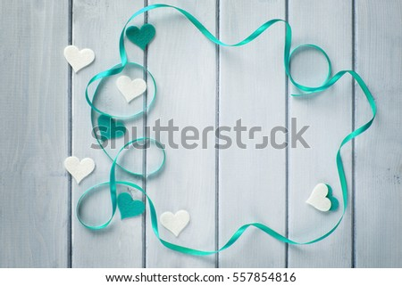 Small hearts on a white wooden background. Decorated with white and cerulean hearts. Valentine love heart conception