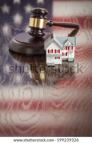 Small House and Gavel on Wooden Table with American Flag Reflection. - stock photo