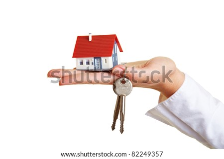Small house and keys on palm of hand - stock photo