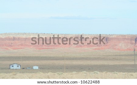 Small house next to colorful red rock outcropping in arizona - stock photo