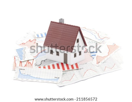 Small house on newspaper charts - stock photo