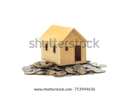 small house standing on coins. The concept of purchase of home.