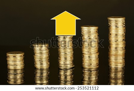 Small house standing on stack of coins isolated on black - stock photo
