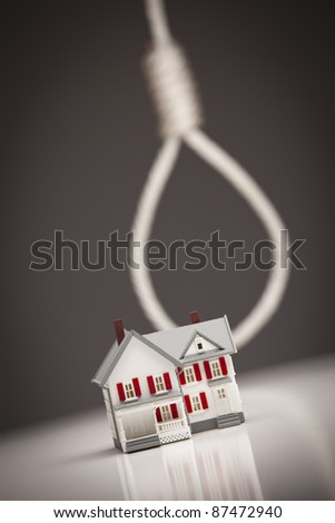 Small House with Hangman's Noose Behind on Grey Background. - stock photo