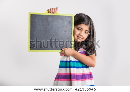 small indian girl holding and presenting blank school slate board, asian girl with school slate board, isolated over white background - stock photo