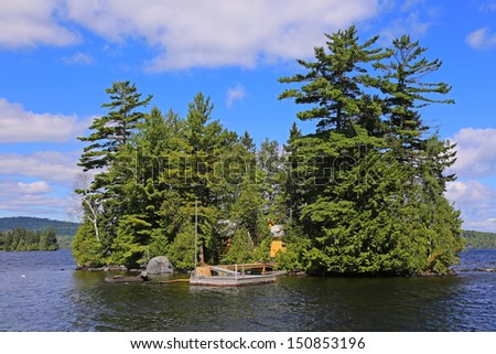 Small island in Moosehead Lake, Maine, with wood cabin, thick foliage & rustic wood dock - stock photo