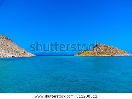 Small island near Agios Nikolaos beach in Symi island in Greece - stock photo