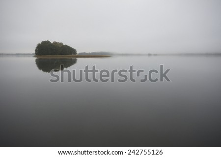 Small island on calm foggy lake water surface during early morning, Mazury, Poland