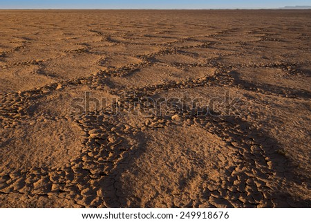 Small islands between the cracked and dried lake bed of lake Iriki in southern Morocco. - stock photo