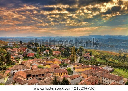 Small italian town among hills under beautiful cloudy autumnal sky at sunset in Piedmont, Northern Italy. - stock photo