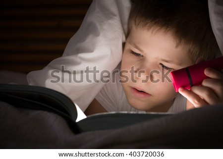 Small kid boy with a smile hiding under a blanket and reading a book with his flashlight in his bedroom at night. Enjoying learning and books. - stock photo