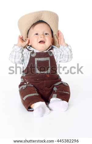small kid in overalls sitting in full length and holds hands a hat white background, isolated - stock photo