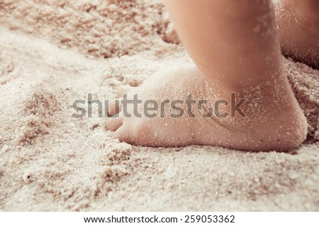 Small kid's foot on the sand - stock photo
