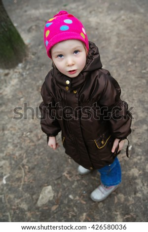 small kid with pleadingly face looking up. Autumn photo