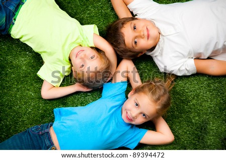 small kids lie on the green grass - stock photo