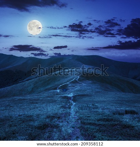 small lake near mountain curve path on a Green Hill at night in full moon light - stock photo