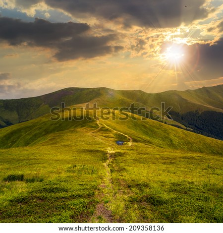 small lake near mountain curve path on a Green Hill at sunset - stock photo