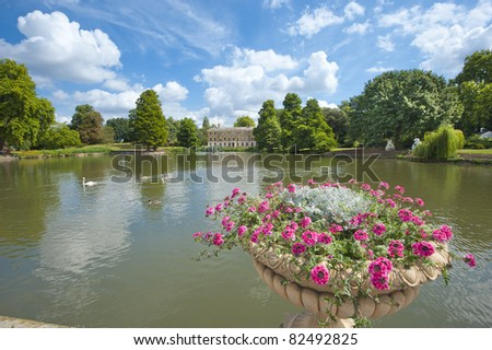 Small lake on an estate in a beautiful rural setting with large flower pot in the foreground