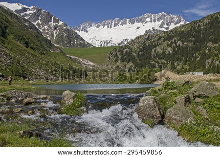 Small lake with waterfall in Goeschener valley in the Urner Alps - stock photo